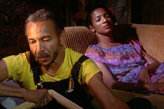 Light skinned man in yellow shirt sitting on ground. To his right is a dark skinned woman in a purple top laying on a couch and staring at camera