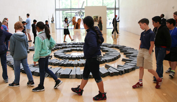 Students walk around a sculpture by Richard Long