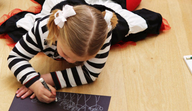 A girl draws in the galleries during a homeschool workshop