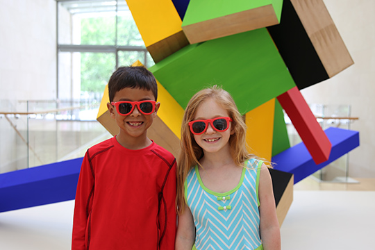 Two children in sunglasses, a boy and girl stand smiling in front of a colorful Joel Shapiro sculpture