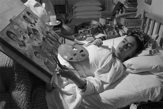 Frida Kahlo painting in her bed