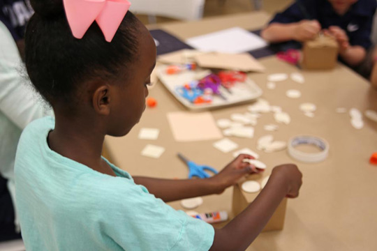 A girl makes art at a homeschool workshop
