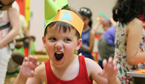 A little boy shows off a dinosaur hat he made at Target First Saturday
