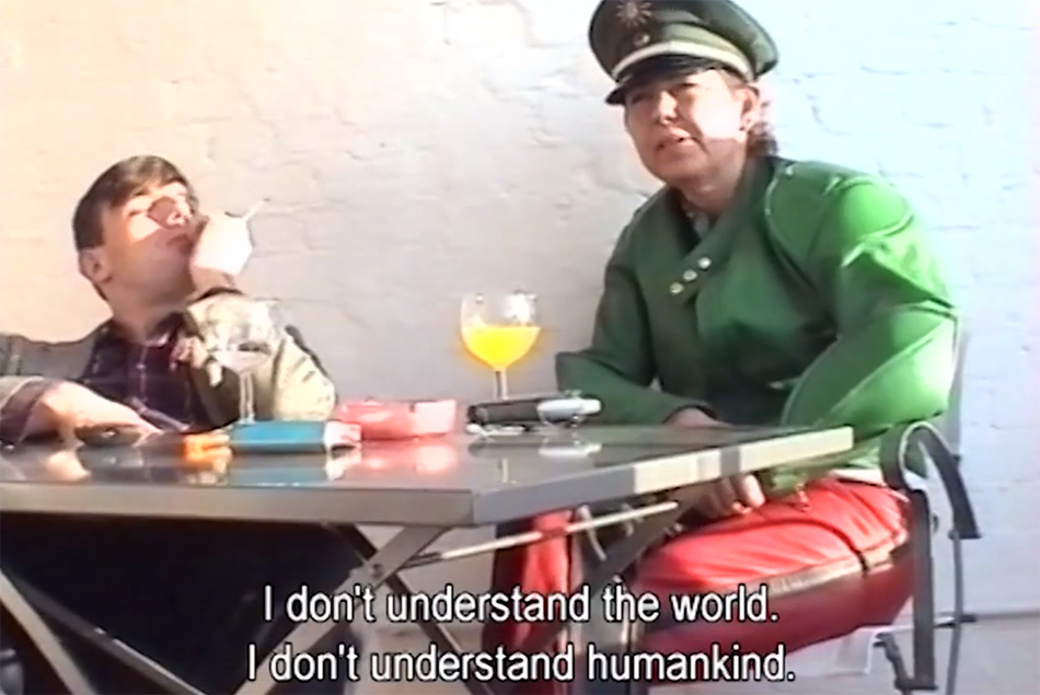 "A still shot of a pair  (including Genzken in character) sitting at a sparse table from the film, ""Warum ich keine Interviews gebe (Why I Don't Give Any Interviews) 2003"""