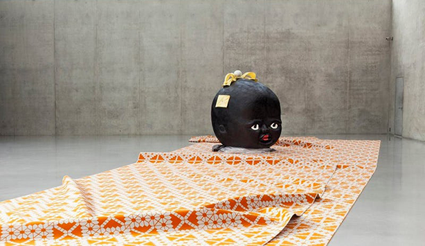 The giant disembodied head of a cartoonish black baby on a orange carpet stares out at the viewer