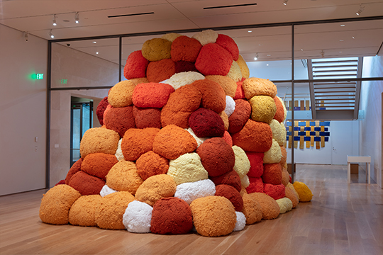 A sculptural installation by Sheila Hicks titled 'Sentinel of Saffron'