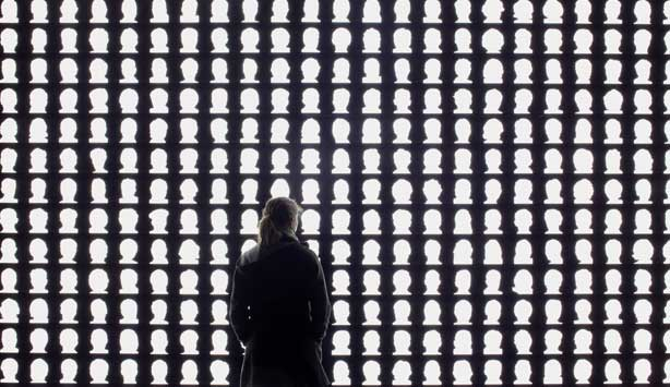 Viewer examines artwork of white silhouetted of heads on an illuminated black background, entitled The Geometry of Conscience, 2010 by Alfredo Jaar