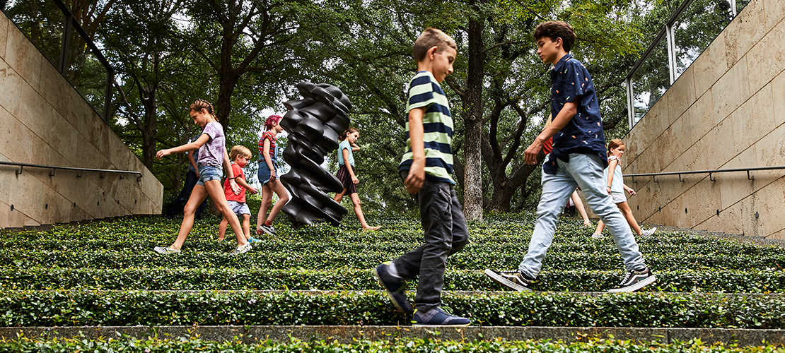 In the garden at the Nasher Sculpture Center young children walk across the terrace steps surrounded by vegetation